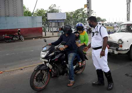 Kolkata: Police personnel intercept commuters at the Howrah Bridge in Kolkata during a complete COVID-19 lockdown being observed across West Bengal, on Aug 8, 2020. (Photo: Kuntal Chakrabarty/IANS)