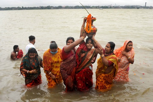 Kolkata: Devotees perform rituals on the banks of Ganga river during Nabapatrika Snan on Maha Saptami during Durga Puja celebrations, in Kolkata on Oct 23, 2020. On this day the rituals start before daybreak. Nine kinds of plants are worshipped. This Nabapatrika (nine leaflets mostly tied together) is given a bath, prior to dawn, in the holy river Ganga or by any nearby lake or pond along with the Kolabou (banana tree) as per rituals it signifies the wife of Lord Ganesha. The priest takes the tree to the pandal, accompanied by a grand procession, which includes many percussionists. The stem of the banana tree is draped in a new yellow cloth with a red border saree and is placed next to Lord Ganesha. (Photo: Kuntal Chakrabarty/IANS)